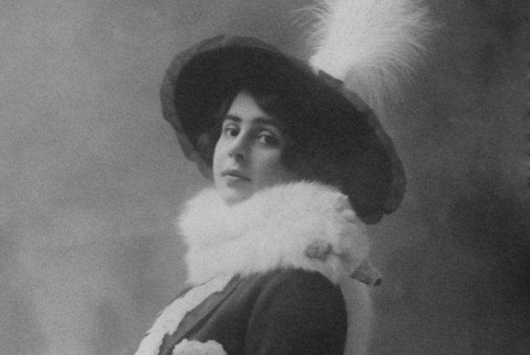 Czarno białe zdjęcie kobiety w eleganckim kapeluszu i płaszczu